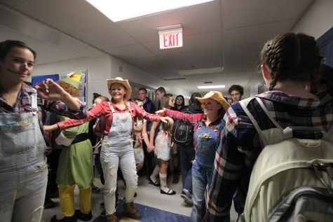 Often during senior Halloween, groups that dress as an ensemble 'perform' during passing time between classes, as these farmer/scarecrow students did on Monday.