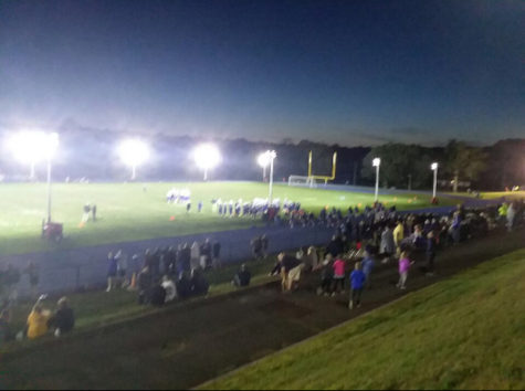 The lights shine over the football field as crowds gather to watch the first game of Lewis Mills football season.