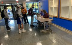 Students line up Thursday morning to purchase tickets to Saturdays Homecoming dance, the first indoor, full-school social event since the pandemic began. Principal Chris Rau and school secretary Ann Marie Dixon have a closely guarded list of students information, including proof of vaccination, recent recovery from Covid or a negative test result that they hope will make the dance a safer environment.